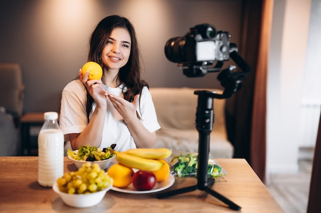 Blogger di cibo sano giovane donna che cucina fresca di frutta insalata vegana in studio di cucina che filma tutorial sulla fotocamera per canale video giovane influencer femminile mostra il suo amore per un'alimentazione sana