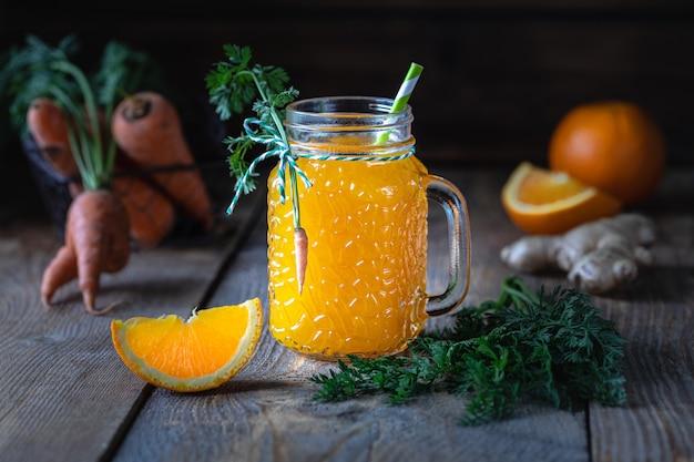 Cibo salutare. carote e succo di carota con zenzero arancione in un barattolo di vetro in un cestello di metallo su uno sfondo di legno scuro