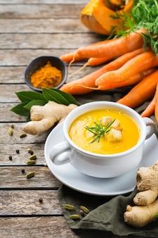 Cibo sano, concetto di mangiare pulito. zuppa cremosa di verdure autunnali piccanti stagionali zucca e carote con ingredienti su un tavolo in legno rustico.