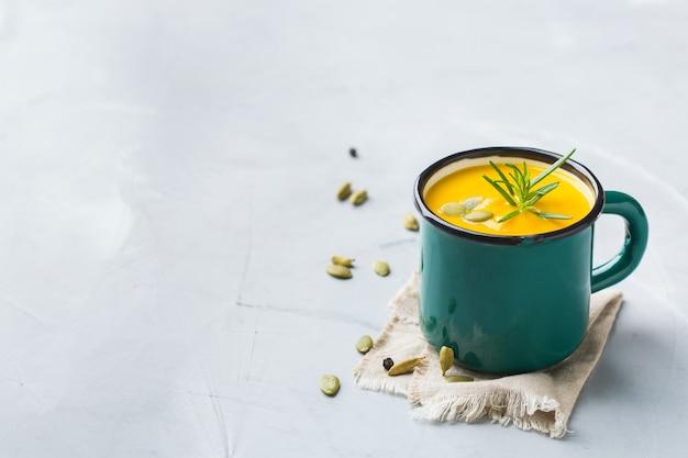 Cibo sano, concetto di mangiare pulito. zuppa cremosa di verdure autunnali piccanti stagionali di zucca e carote con ingredienti su un tavolo. copia lo sfondo dello spazio