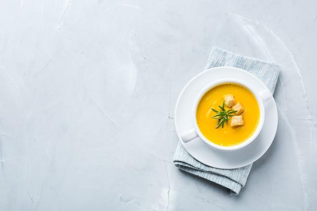 Cibo sano, concetto di mangiare pulito. zuppa cremosa di verdure autunnali piccanti stagionali di zucca e carote con ingredienti su un tavolo. disposizione piatta, copia dello sfondo dello spazio