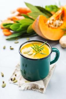 Cibo sano, concetto di mangiare pulito. zuppa cremosa di verdure autunnali piccanti stagionali di zucca e carote con ingredienti su un tavolo.