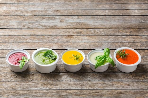 Cibo sano, concetto di mangiare pulito. varietà di zuppe cremose di verdure autunnali colorate di stagione con ingredienti. zucca, broccoli, carota, barbabietola, patata, pomodoro, spinaci. copia spazio