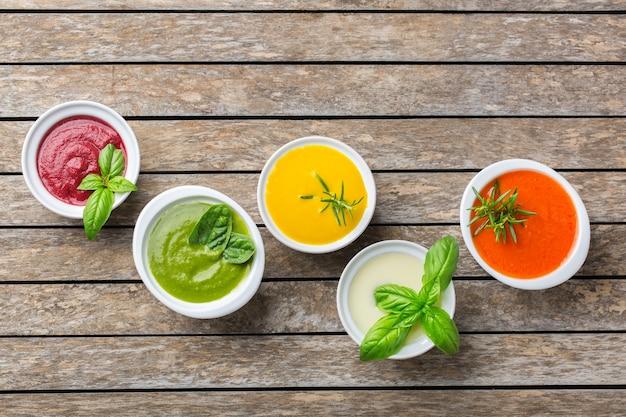 Cibo sano, concetto di mangiare pulito. varietà di zuppe cremose di verdure autunnali colorate di stagione con ingredienti. zucca, broccoli, carota, barbabietola, patata, pomodoro, spinaci. disposizione piatta, copia spazio
