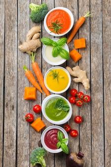 Cibo sano, concetto di mangiare pulito. varietà di zuppe cremose di verdure autunnali colorate di stagione con ingredienti. zucca, broccoli, carota, barbabietola, patata, pomodoro, spinaci. lay piatto