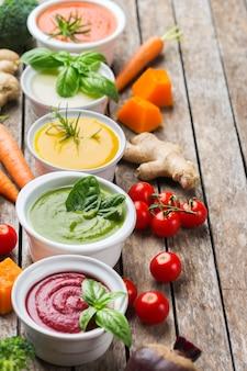 Cibo sano, concetto di mangiare pulito. varietà di zuppe cremose di verdure autunnali colorate di stagione con ingredienti. zucca, broccoli, carota, barbabietola, patate, pomodoro, spinaci