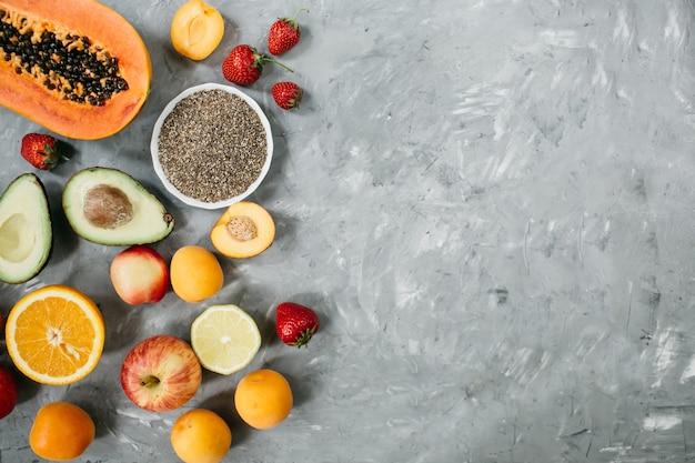 Selezione di cibi sani e puliti: frutta, bacche, semi di chia, superfood su sfondo grigio cemento.vista dall'alto, piatto foto di alta qualità