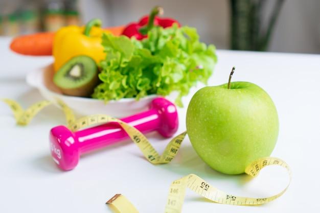 Cibo sano selezione di cibi puliti con frutta, verdura, manubri e metro a nastro. selezione di cibi sani. concetto di mangiare pulito. concetto di dieta