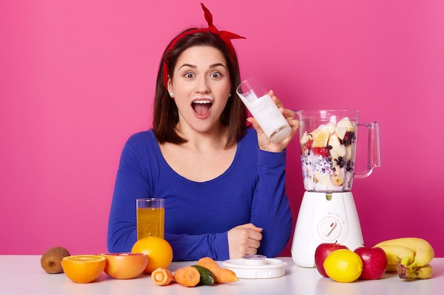Concetto di cibo sano. primo piano di una giovane donna utilizza bacche e banane per fare il frullato. la parete rosa dello studio della signora stupita di nuovo beve il latte mentre prepara la coktail. concetto di stile di vita sano.