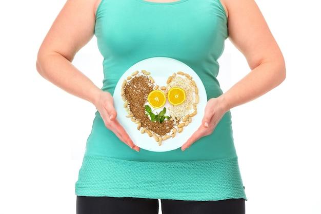 Il cibo sano. il concetto di dieta e stile di vita sano per la donna grassa. il piatto con frutta, verdura e noci