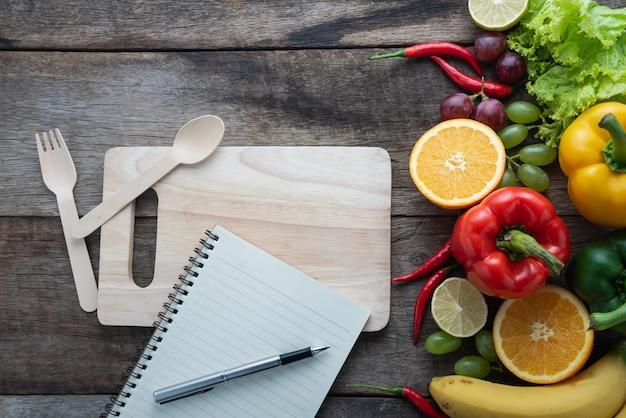 Concetto di cibo sano di verdure biologiche fresche e sfondo scrivania in legno.