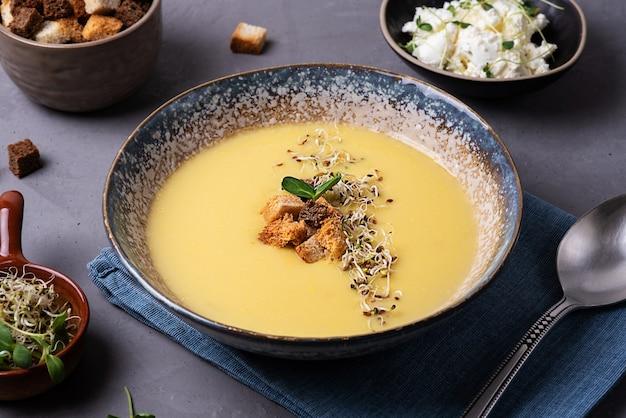 Concetto di cibo sano, zuppa di crema di zucca vegetariana fatta in casa con crostini di pane e microgreens.