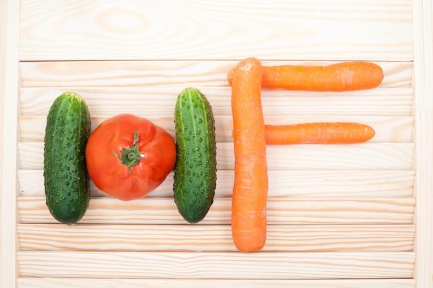 Concetto di cibo sano. le lettere h e f fatte di cetrioli, pomodoro e carote. sfondo di verdure.