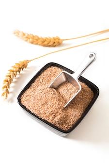 Crusca di frumento organica di concetto sano dell'alimento in tazza ceramica nera con l'orecchio del grano isolato su bianco