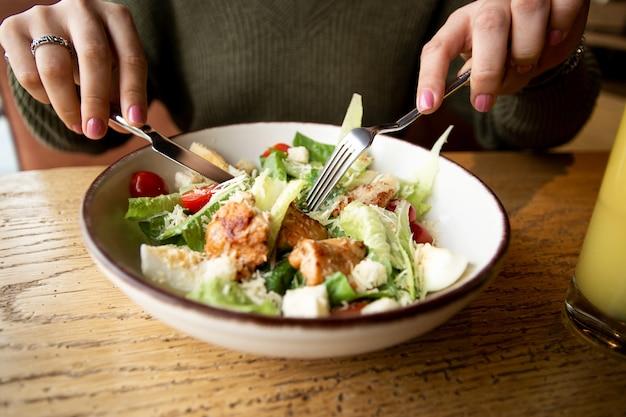 Concetto di cibo sano. vista dall'alto. insalata caesar sulla zolla bianca. vista ravvicinata delle mani della donna caucasica