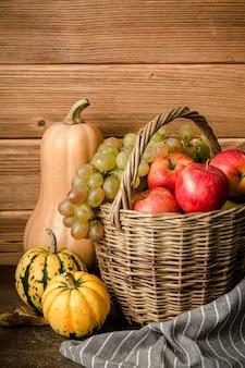 Contenuto alimentare sano, natura morta di zucca, mini zucche, cesto di vimini con uva verde e gialla, mele rosse, su un tavolo scuro, con asciugamano marrone, fondo in legno