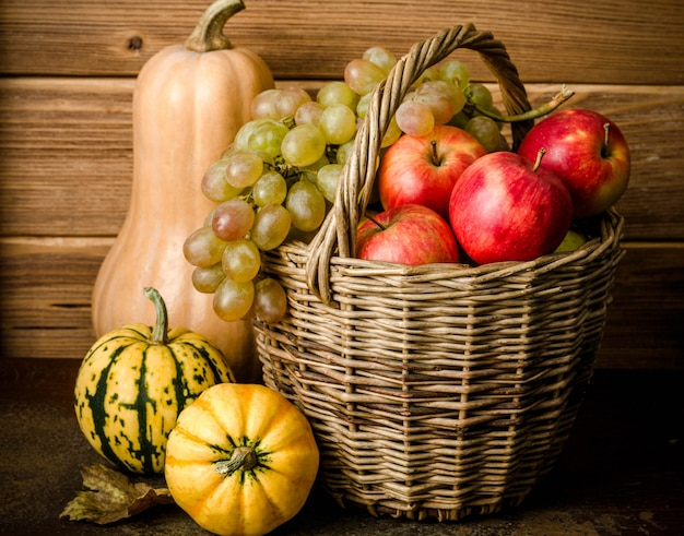Contenuto alimentare sano, natura morta di zucca, mini zucche, cesto di vimini con uva verde e gialla, mele rosse, su un tavolo scuro, sfondo di legno, orizzontale