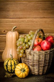 Contenuto alimentare sano, natura morta di zucca, mini zucche, cesto di vimini con uva verde e gialla, mele rosse, su un tavolo scuro, sfondo di legno