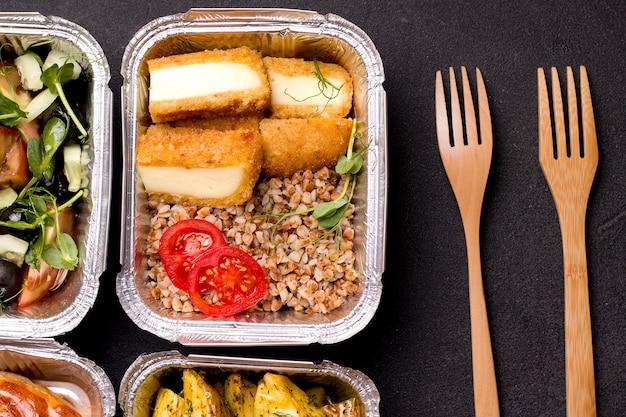Concetto di consegna di cibo sano. in un contenitore porridge con verdure e formaggio fritto