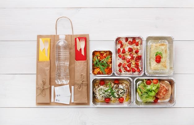 Consegna di cibo sano, pasti giornalieri e spuntini. nutrizione, verdure, farina d'avena ai frutti di bosco, carne e bottiglia d'acqua in scatole di alluminio e pacchetto di carta marrone. vista dall'alto, piatto laici in legno bianco con spazio di copia