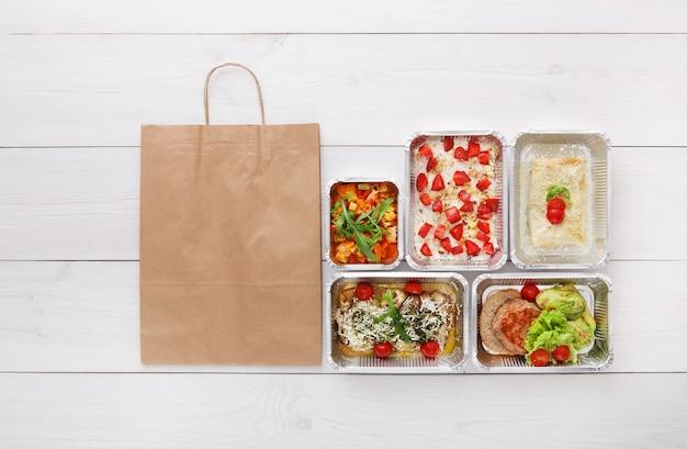 Consegna di cibo sano, pasti giornalieri e spuntini. nutrizione, verdura, carne e frutta in scatole di alluminio e pacchetto di sacchetti di carta marrone. vista dall'alto, piatto laici in legno bianco con spazio di copia