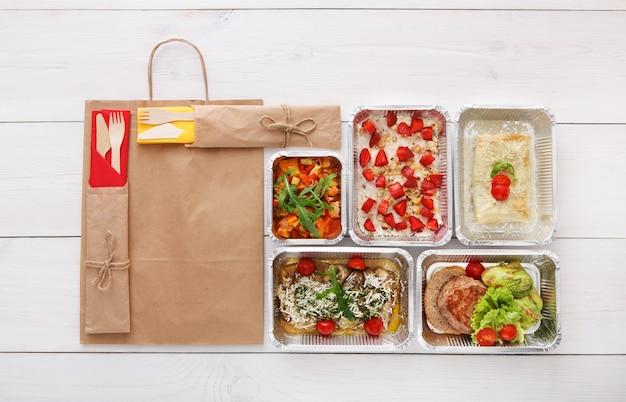 Consegna di cibo sano, pasti giornalieri e spuntini. nutrizione, verdura, carne e frutta in scatole di alluminio e pacchetto di carta marrone. vista dall'alto, piatto laici in legno bianco con spazio di copia