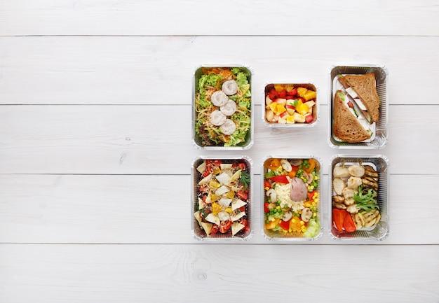 Consegna di cibo sano, pasti giornalieri e spuntini. nutrizione, verdura, carne e frutta in scatole di alluminio. vista dall'alto, piatto laici in legno bianco con spazio di copia
