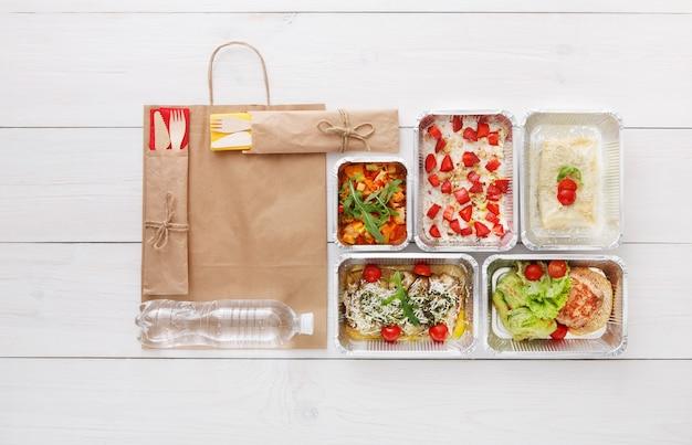 Consegna di cibo sano, pasti giornalieri e spuntini. nutrizione, verdure, carne, bottiglia d'acqua e frutta in scatole di alluminio e pacchetto di carta marrone. vista dall'alto, piatto laici in legno bianco con spazio di copia