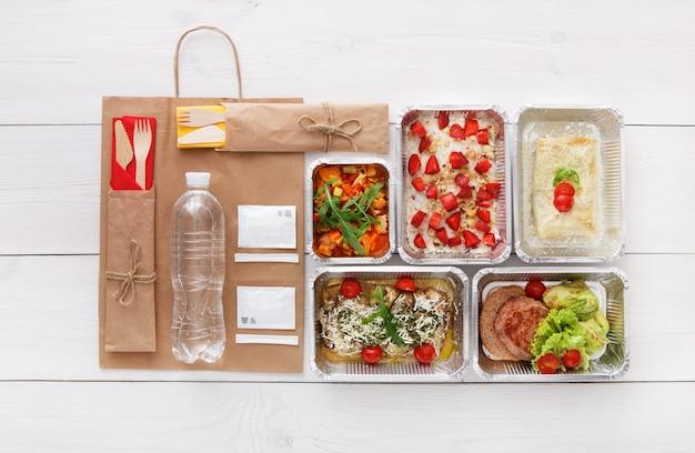 Consegna di cibo sano, pasti giornalieri e spuntini. nutrizione, verdure, carne, bottiglia d'acqua e frutta in scatole di alluminio e pacchetto di carta marrone. vista dall'alto, piatto in legno bianco