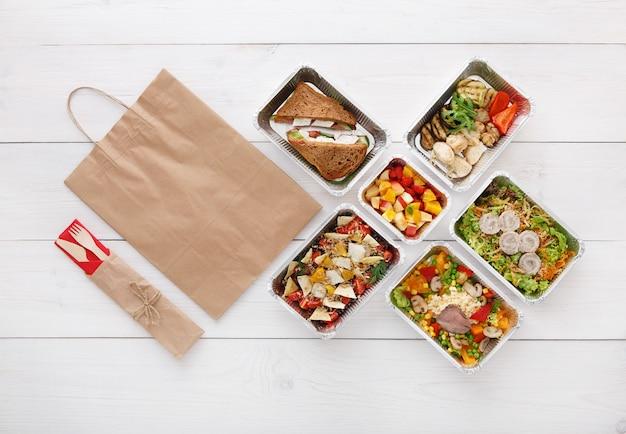 Consegna di cibo sano. porta via il cibo. verdure, carne e frutta in scatole di alluminio, posate, acqua e confezione di carta marrone. vista dall'alto, piatto laici in legno bianco con spazio di copia