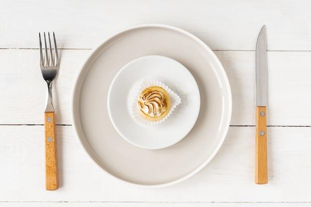 Concetto di dieta e cibo sano. piccolo dessert su un grande piatto servito con forchetta e coltello sul tavolo bianco.