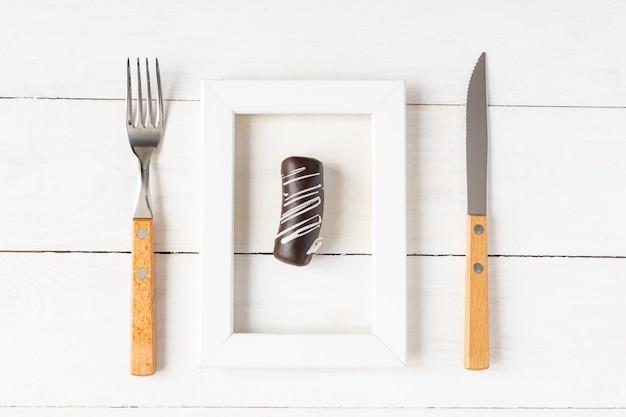 Concetto di dieta e cibo sano. piccolo dessert in una cornice per foto servito con forchetta e coltello sul tavolo bianco.