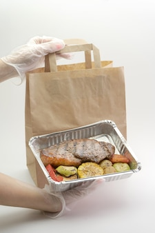 Cibo sano in una scatola di alluminio, consegna accurata, mani guantate da donna che tengono cibo su una parete isolata