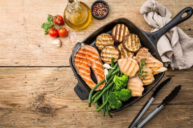 Bistecca di salmone alla griglia cibo sano, pollo e verdure in una padella per grigliare su una superficie di legno, vista dall'alto