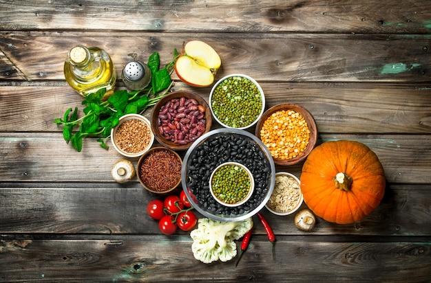 Cibo salutare. un sano assortimento di frutta e verdura con legumi. su uno sfondo di legno.