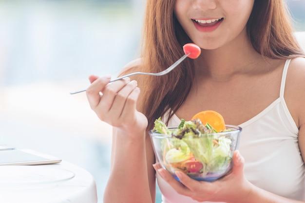 Stile di vita sano cibo sano con giovane donna felice che mangia insalata biologica di ingredienti freschi verdi.