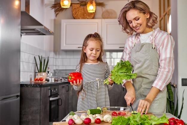 Cibo sano a casa. felice famiglia caucasica in cucina, madre e figlia bambino stanno preparando il pasto per la cena