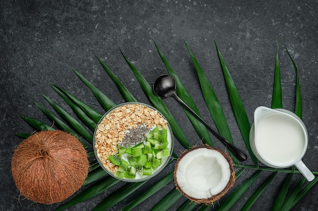 Cibo sano ciotola di farina d'avena con latte di cocco e kiwi sulla superficie scura
