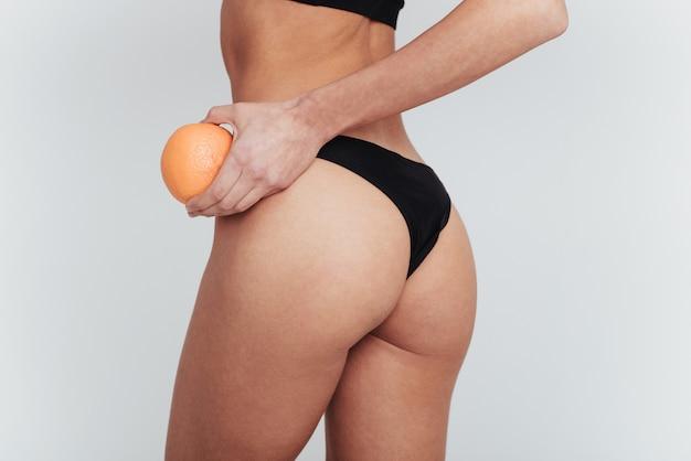 Cibo salutare. foto di particelle di ragazza in biancheria intima nera in piedi al muro bianco e tenendo l'arancia.