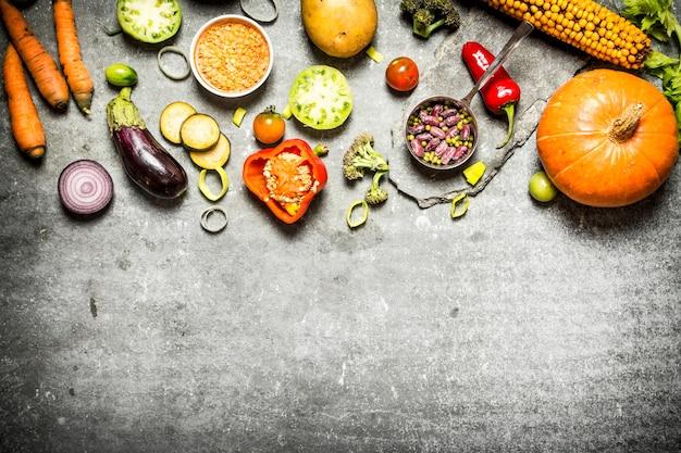 Cibo salutare. pezzi di verdure fresche e fagioli. sul tavolo di pietra.