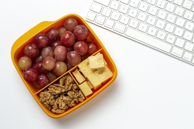 Cibo sano in contenitori di plastica pronti da mangiare con formaggio, uva e noci sul tavolo di lavoro.