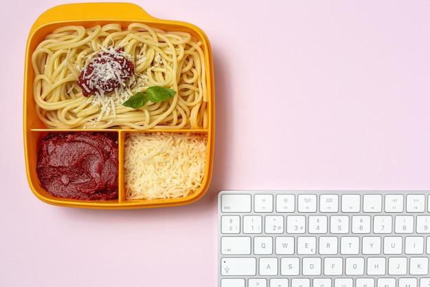 Cibo sano in contenitori di plastica pronti da mangiare con spaghetti fatti in casa con pomodoro, formaggio e basilico sul tavolo di lavoro. cibo italiano. portare via.
