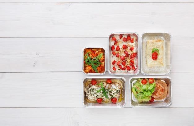 Consegna di cibo sano al ristorante, pasti giornalieri e spuntini. nutrizione, verdura, carne e frutta in scatole di alluminio. vista dall'alto, piatto laici in legno bianco con spazio di copia