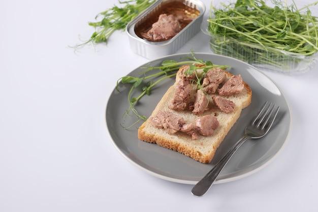 Cibo sano, panino con fegato di merluzzo e microgrine di piselli su un piatto grigio su un tavolo bianco, primo piano