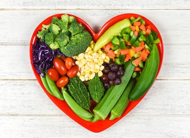 Selezione di alimenti sani mangiar pulito per la vita del cuore dieta colesterolo concetto di salute insalata di frutta fresca e verdure verdi miste vari fagioli noci grano sul piatto cuore per cibo sano cucina vegana