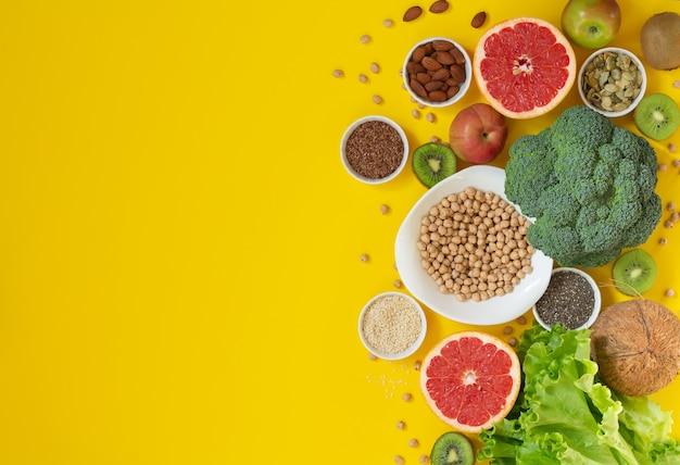 Selezione di cibi sani con frutta verdura semi superfood noci su sfondo giallo spazio per il testo
