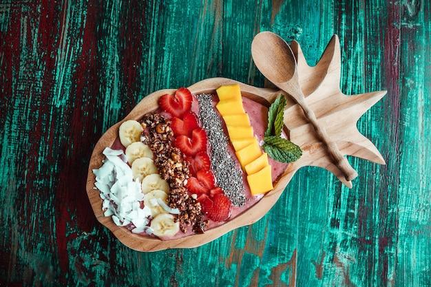 Cibo sano sulla ciotola del frullato a forma di ananas con frutta a fette, mango, banana, cocco e semi