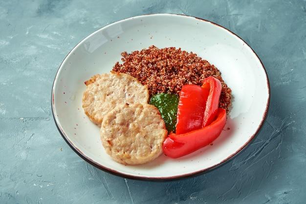 Cibo sano - hamburger di pollo al vapore (cotolette) con quinoa e salsa al pesto in una ciotola bianca su sfondo grigio