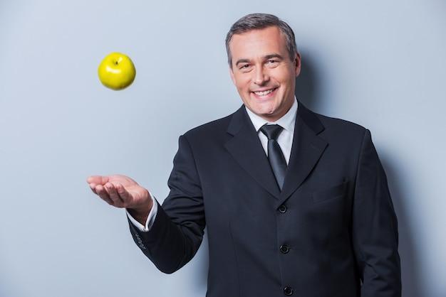 Cibo sano per il successo. fiducioso uomo maturo in abiti da cerimonia che lancia una mela verde e sorride mentre sta in piedi su uno sfondo grigio