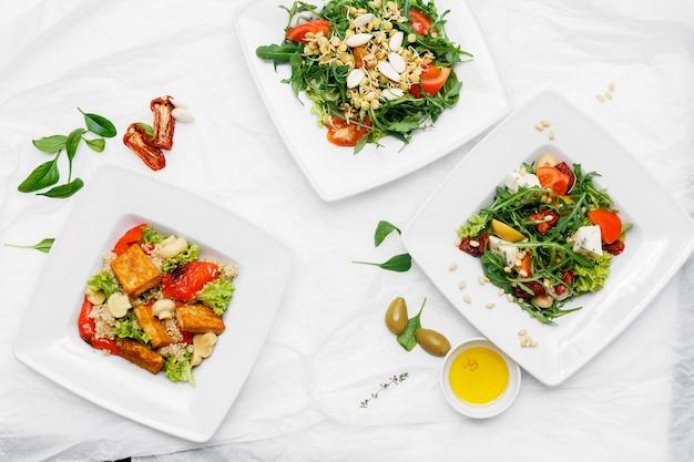 Cibo salutare. tre piatti bianchi. insalata di pomodoro, rucola, spinaci, olive, pepe. sfondo bianco